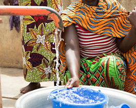 An African lady pumping clean water from a community borehole into a blue bucket. Changing climatic conditions and consumption trends, threaten water security.
