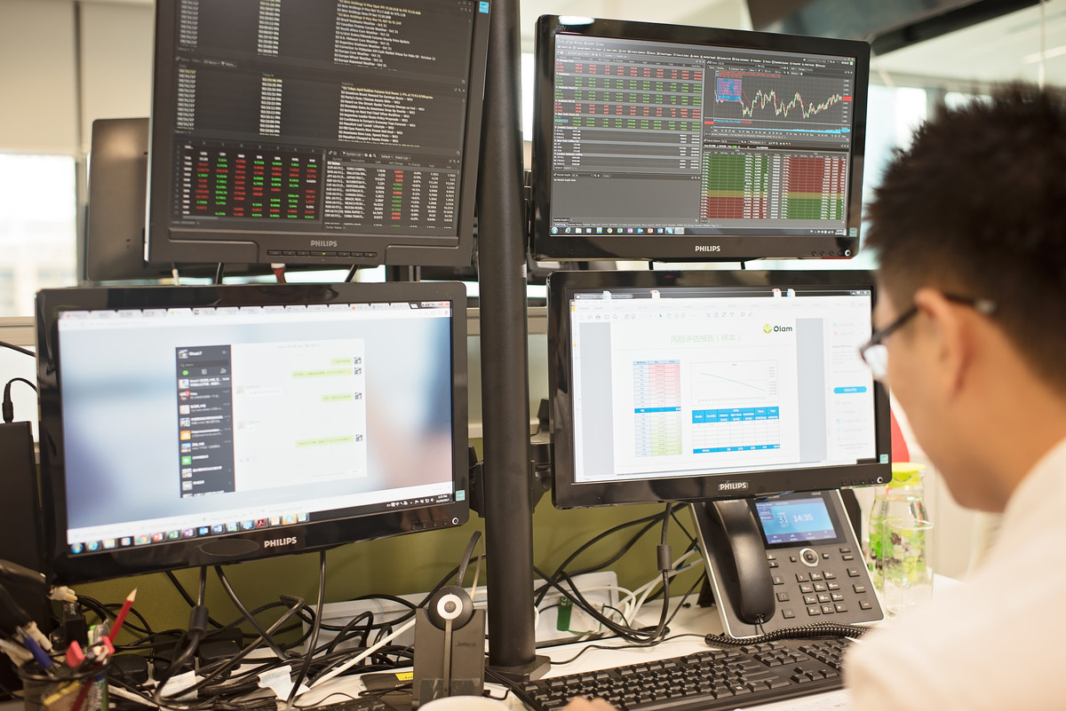 Olam trader working on multiple screens in his office in Singapore, one of the many roles available at the organisation.