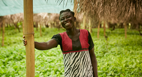 Female farmer in Ghana, with her crops growing behind her, Olam.