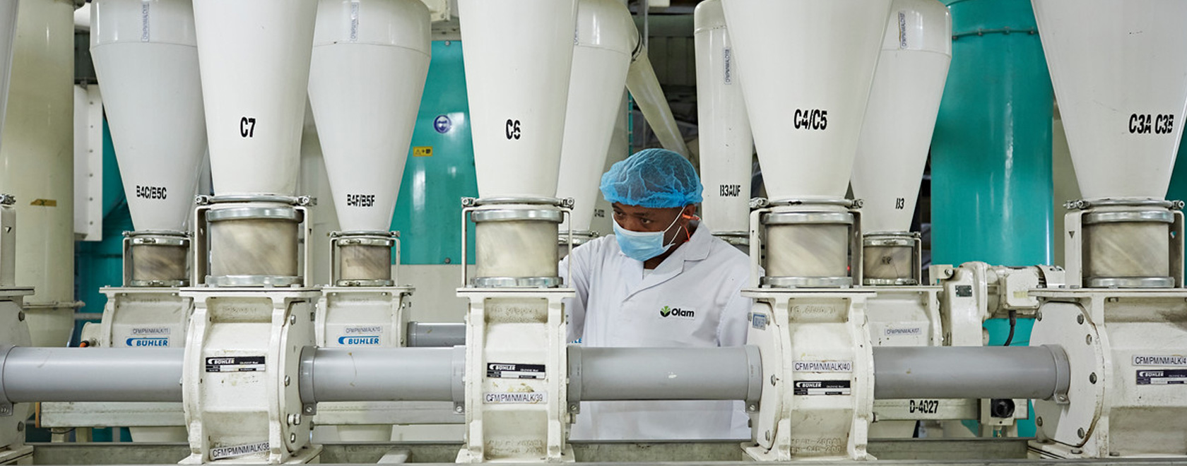 Olam employee checking flour quality on individual shoots in the CFM mill, Nigeria.
