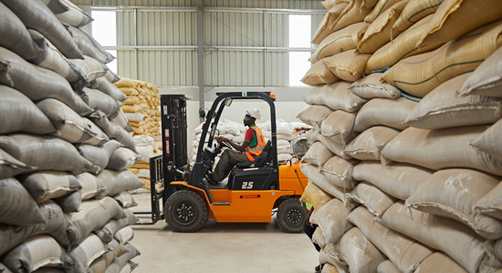 A forklift moving between stacks of animal feed in an Olam warehouse, Nigeria.