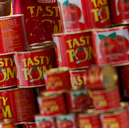 A stack of Tasty Tom tins full of tomato paste, Olam also manufactures pasta, biscuits, yoghurt drinks and edible oils for African markets.