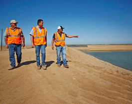 Three engineers reviewing a dam, installed to mitage impacts of climate change on water management, USA, Olam.
