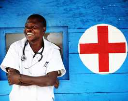 An Olam-employed Doctor standing in front of a medical centre, one of many of our health initiatives in Africa, Olam.